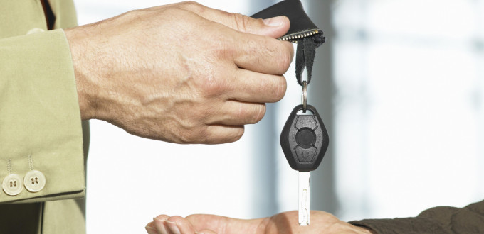 Car salesman handing car keys to man in showroom, close-up